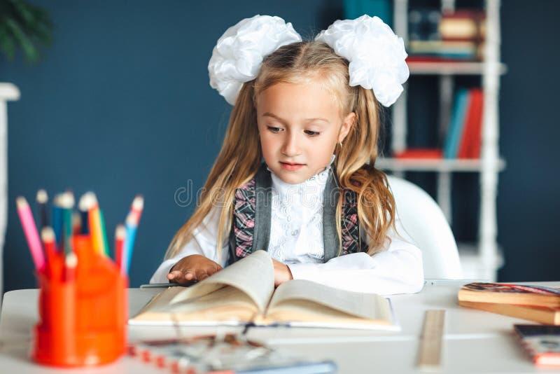 家庭工作是一个难题测试一级回到学校概念 有猪尾和弓的女孩在一白色女衬衫衬衣生叶 免版税库存图片