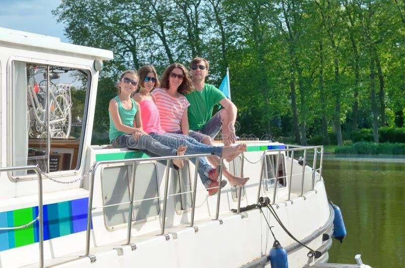 家庭度假、暑假旅行在驳船小船在运河,愉快的孩子和父母获得乐趣在河巡航旅行在居住船 免版税库存照片