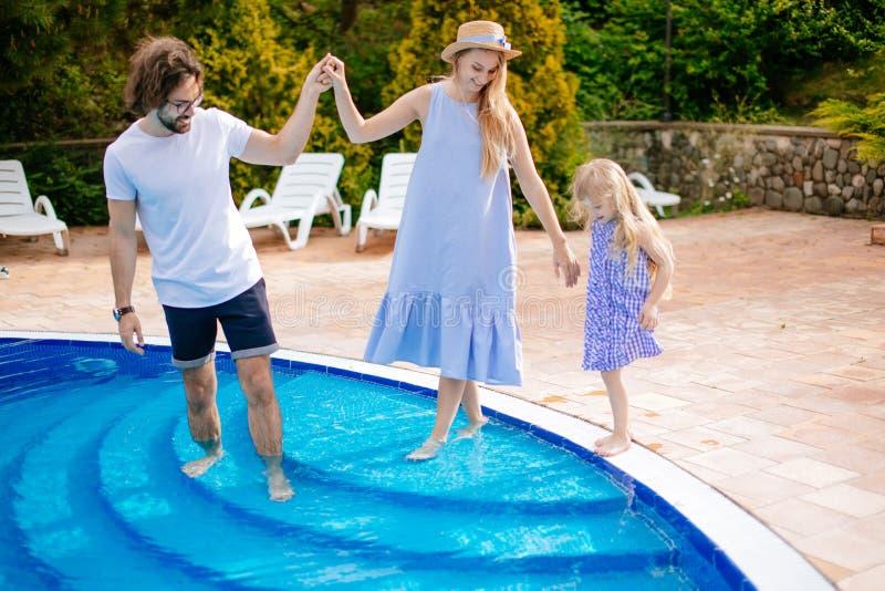 家庭度假在夏天 有孩子的父母获得乐趣在游泳池附近 免版税库存图片