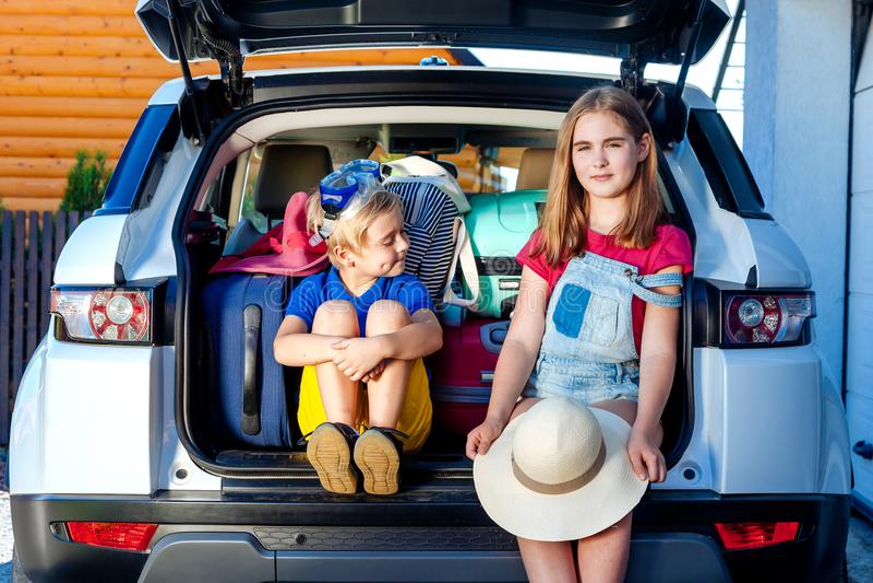 家庭度假手提箱拉布拉多狗女孩男孩孩子行李蓝色桃红色橙色房子太阳夏天行李汽车准备好假日绿化tra 图库摄影