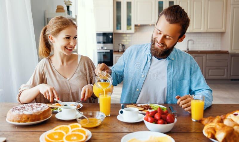 家庭愉快的夫妇食用早餐在厨房在早晨 免版税图库摄影