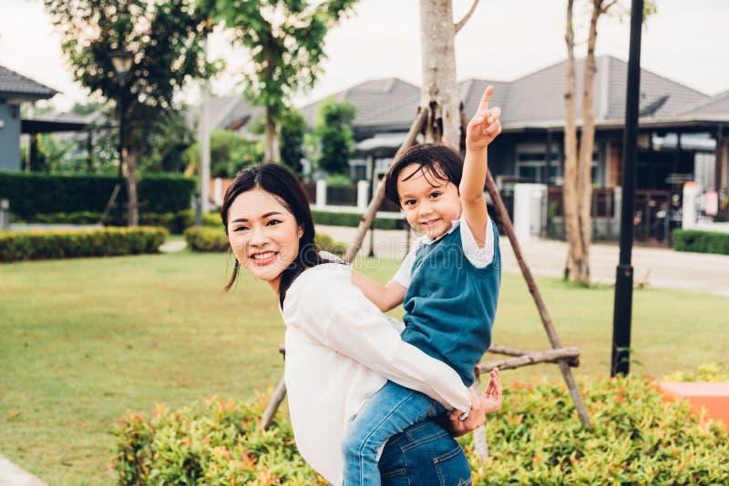 家庭愉快的孩子哄骗儿子演奏乘驾后面肩扛母亲妈妈的男孩幼儿园 库存照片