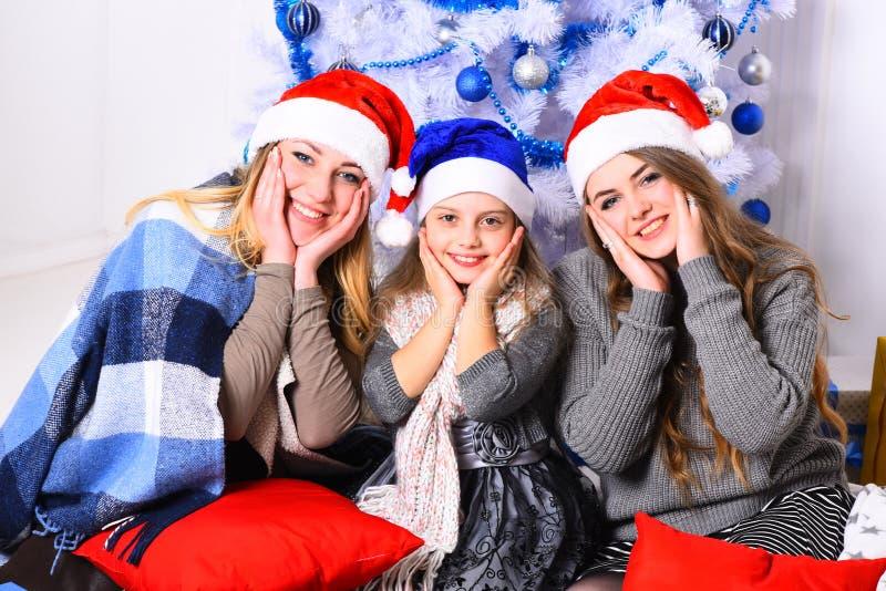 家庭或朋友圣诞老人帽子的在当前箱子附近 图库摄影