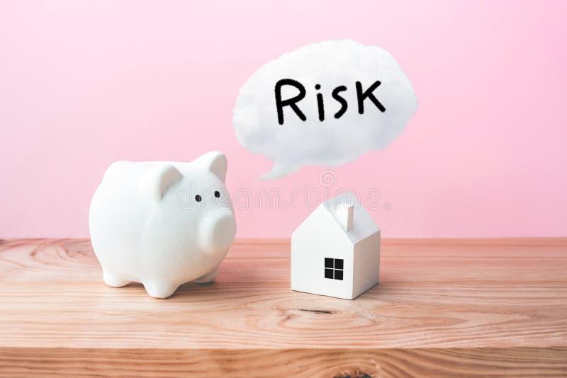 家庭房子大模型和存钱罐有风险文本的在木桌上 库存图片