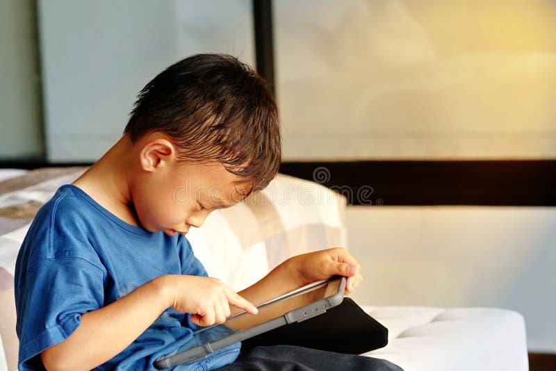 家庭护理和ADHD概念中男孩独自玩智能手机 免版税库存图片