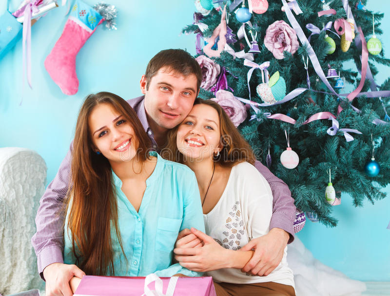 家庭拿着圣诞节礼物和坐地板 库存图片