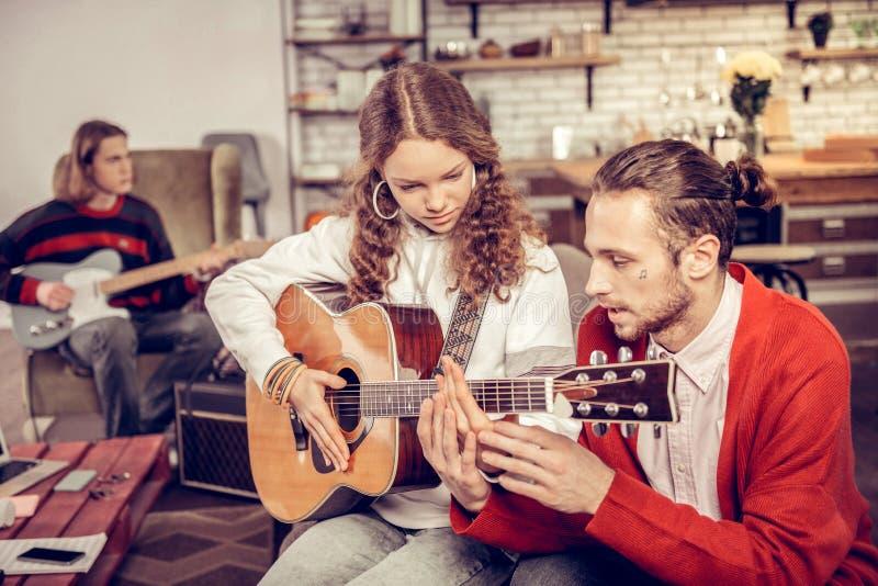 家庭教师弹吉他的教学少年在客厅 图库摄影