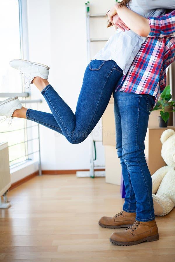 家庭新 滑稽的年轻夫妇享用和庆祝搬到新的家 在新的家空的室的愉快的夫妇  免版税库存照片