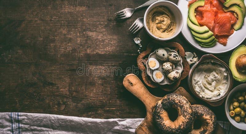 家庭早餐准备用百吉卷面包、三文鱼、鲕梨、新鲜的干酪、hummus和煮熟的鹌鹑蛋在黑暗土气木 库存照片