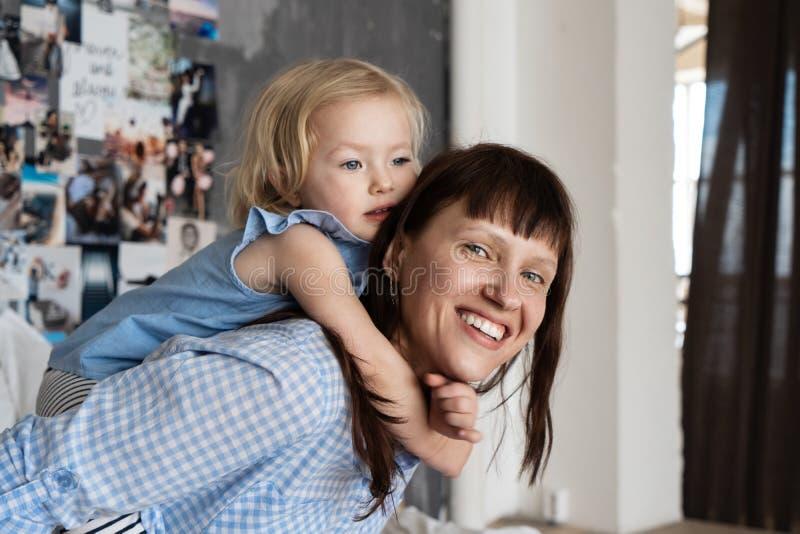 家庭时间:拥抱在床上的妈妈和女儿在卧室 免版税图库摄影