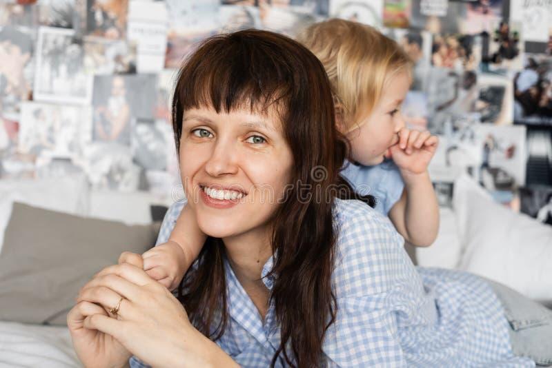 家庭时间:拥抱在床上的妈妈和女儿在卧室 免版税库存照片
