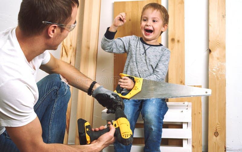家庭时间:爸爸显示他的儿子手工具、一把黄色螺丝刀和一把引形钢锯 他们需要操练和操练委员会为 免版税图库摄影