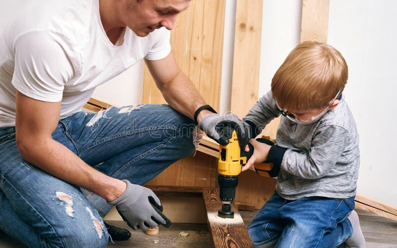 家庭时间:爸爸显示他的儿子手工具、一把黄色螺丝刀和一把引形钢锯 他们需要操练和操练委员会为 免版税库存图片