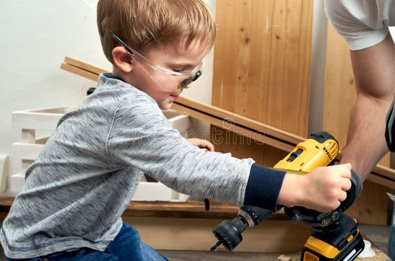 家庭时间:爸爸显示他的儿子手工具、一把黄色螺丝刀和一把引形钢锯 他们需要操练和操练委员会为 库存照片