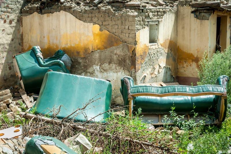 家庭昂贵的皮革家具倾销了损坏的外面被拆毁的和被破坏的别墅房子在后果地震或fl 免版税库存照片