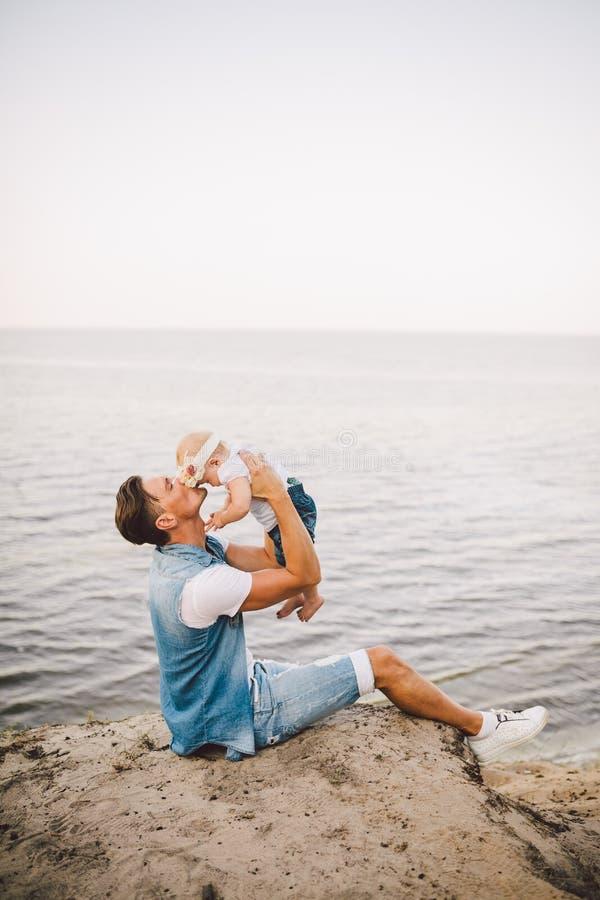 家庭暑假本质上 父亲和一点女儿坐含沙峭壁一年有海的高看法 一个人是 免版税库存图片