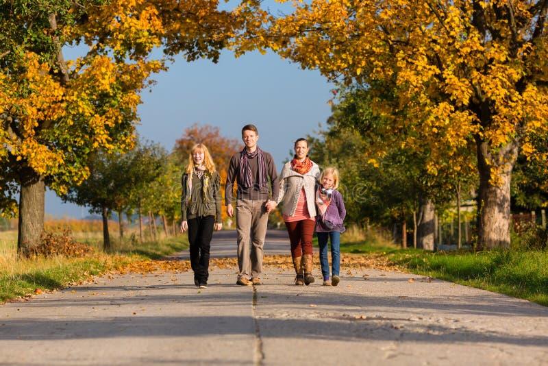 家庭有在五颜六色的树前面的步行在秋天 免版税库存图片