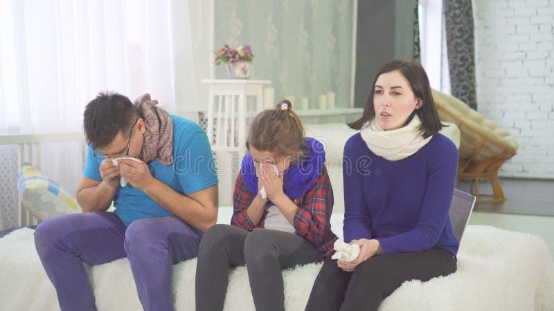 家庭有感冒、妈妈爸爸和女儿喷嚏在家坐床 免版税库存图片
