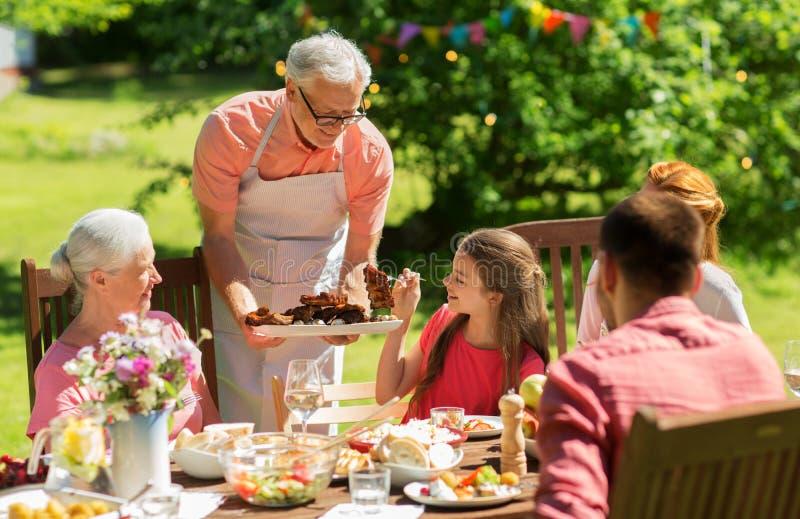 家庭有晚餐或烤肉在夏天庭院 免版税库存图片