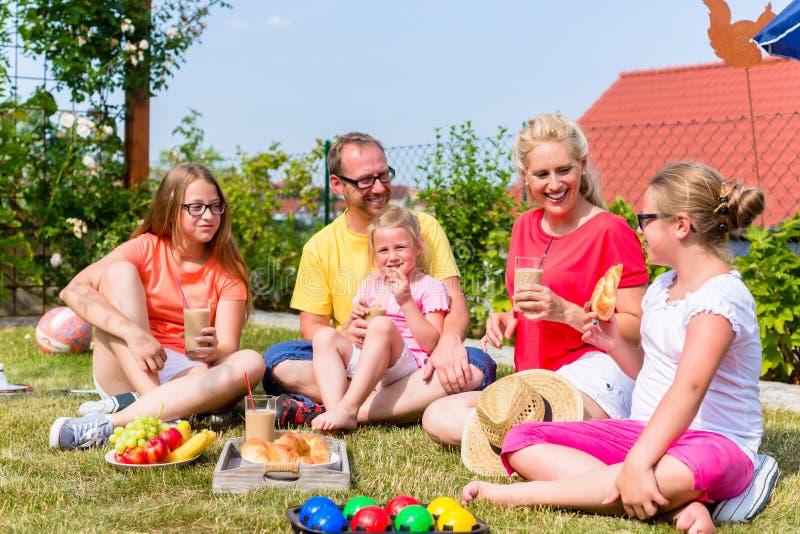 家庭有野餐在他们的家庭院前面  免版税库存图片