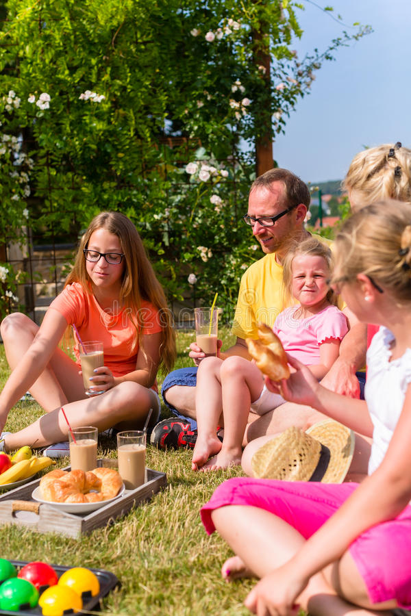 家庭有野餐在他们的家庭院前面  免版税图库摄影