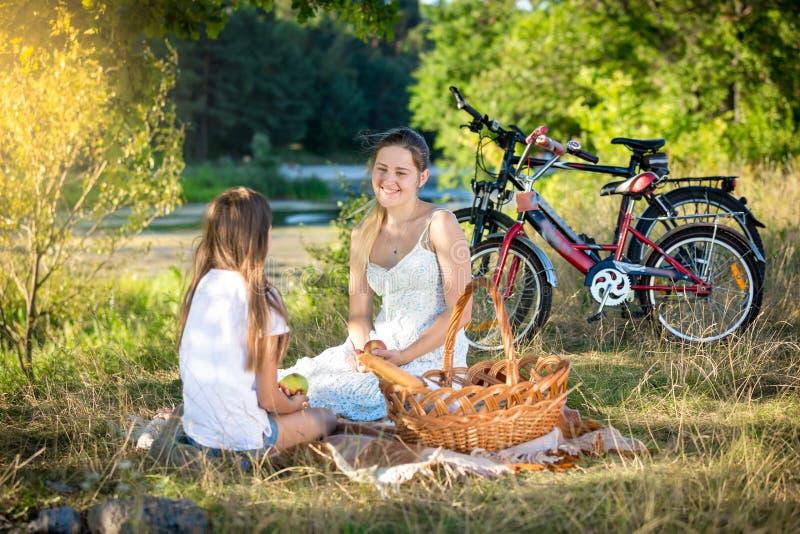 家庭有野餐由河 微笑的母亲和女儿l 免版税库存照片