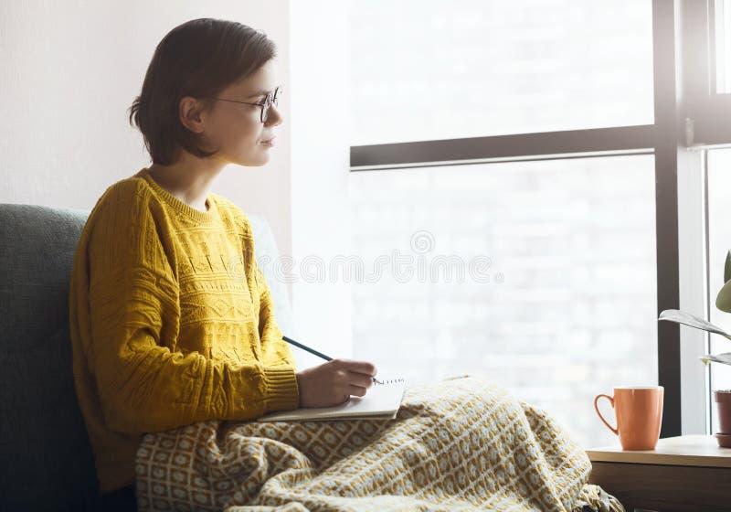家庭检疫中使用铅笔和笔记书写工作或学习笔记的妇女 免版税图库摄影