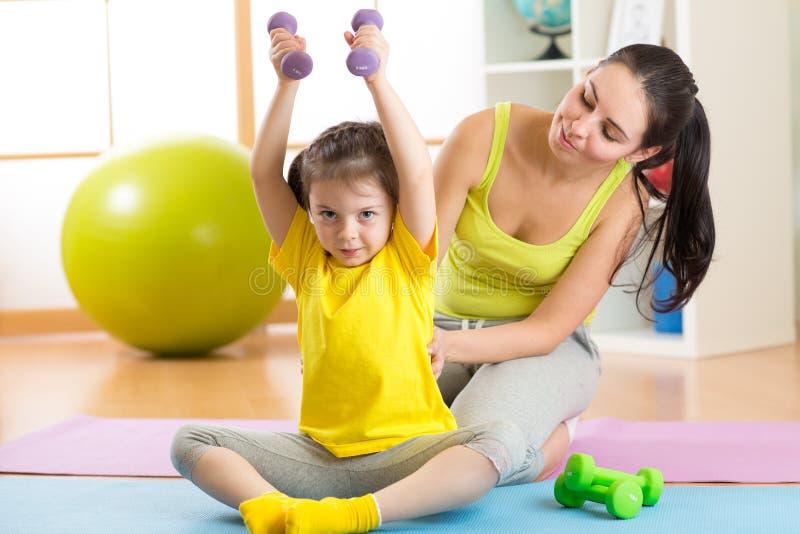 家庭母亲和儿童女儿参与健身,瑜伽,在家行使或体育馆 免版税库存图片