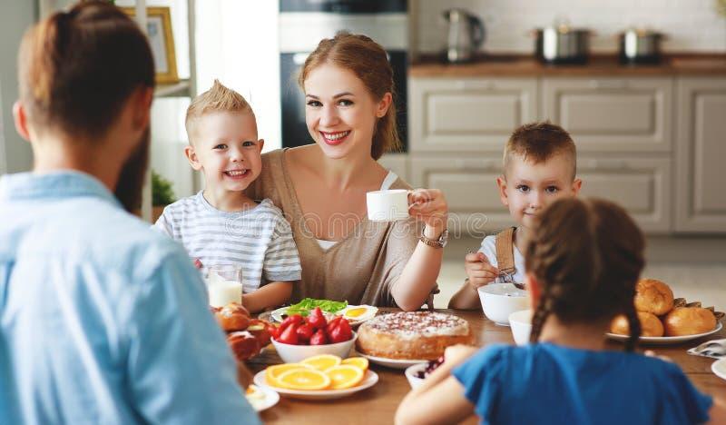 家庭母亲父亲和孩子食用早餐在厨房在早晨 免版税库存图片