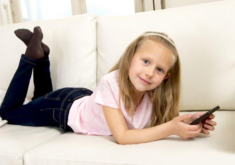 家庭沙发的愉快的白肤金发的小女孩使用手机的互联网app 免版税库存照片