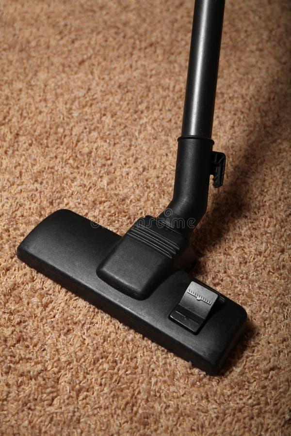 家庭清洁,在地毯的吸尘器 免版税库存图片