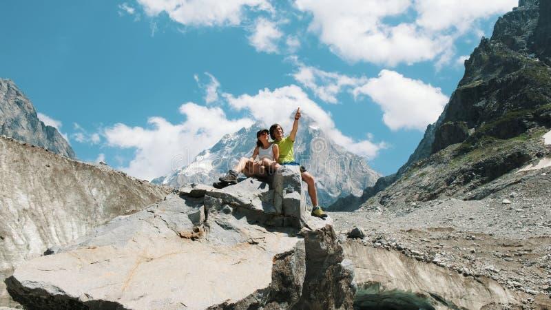 家庭游人已婚夫妇坐岩石并且享受山景 人拥抱远足的一名妇女和 库存图片