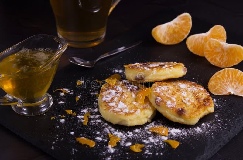 家庭烹饪和健康吃的概念 在乳酪蛋糕的顶视图用葡萄干和蜜桔 附近新鲜的蜂蜜从 免版税库存照片