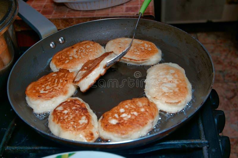 家庭烹饪食物 新鲜的鲜美油炸馅饼或薄煎饼在平底锅油煎并且移交与叉子 库存图片