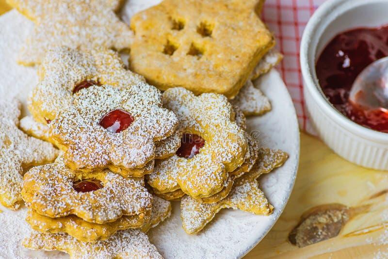 家庭焙制的姜饼和一种油脂含量较高的酥饼各种各样的形状星议院花用果酱Linzer搽粉了 板材木头表 免版税库存照片