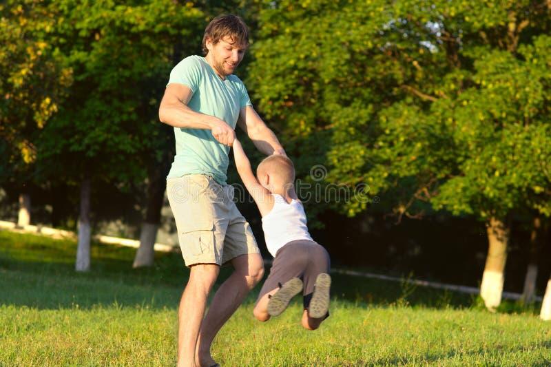 家庭父亲人和演奏室外公园的儿子男孩 免版税图库摄影