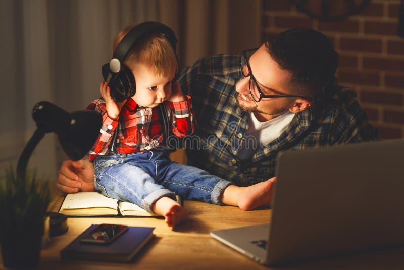 家庭父亲和听到与耳机的音乐的儿子婴孩 免版税图库摄影