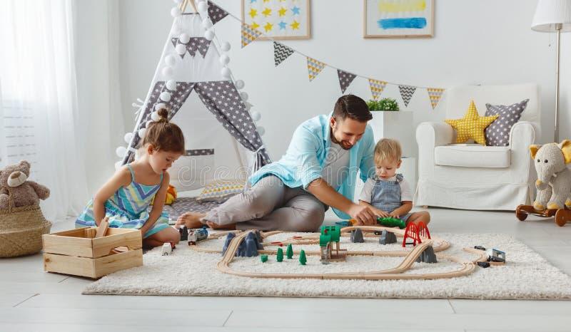 家庭父亲和孩子播放在游戏室的一条玩具铁路 免版税库存照片