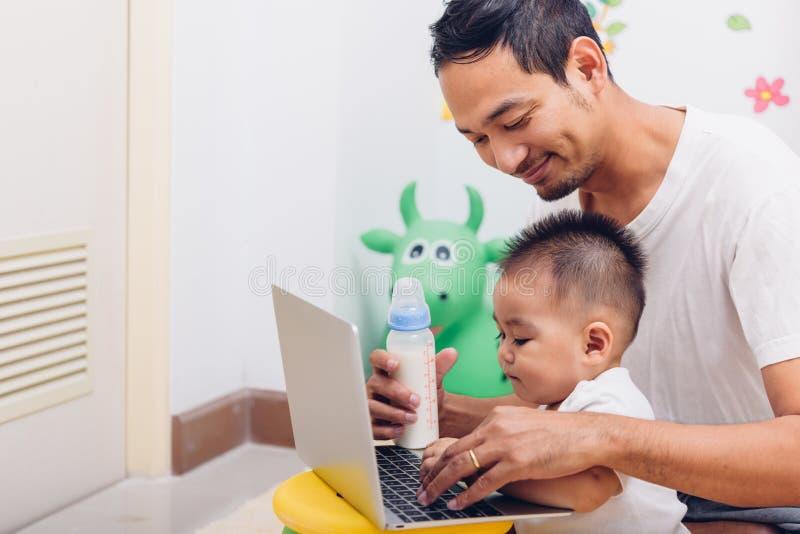 家庭父亲爸爸吃哺乳瓶牛奶男婴儿子drinki 库存照片
