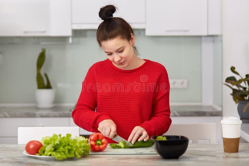 家庭生活和母性概念 繁忙的孕妇切开做的沙拉,在现代公寓的姿势菜反对 免版税库存图片