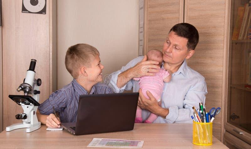 家庭生活方式概念 做家庭作业的微笑的男孩使用lapto 库存图片