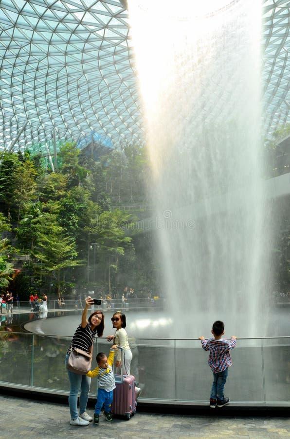 家庭由瀑布采取selfie照片和树在珠宝樟宜机场新加坡 免版税库存照片