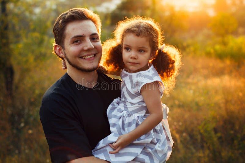 家庭画象四在与小女孩的秋天森林公园孪生 愉快的人民,微笑和亲吻 温暖的晚上阳光 库存图片