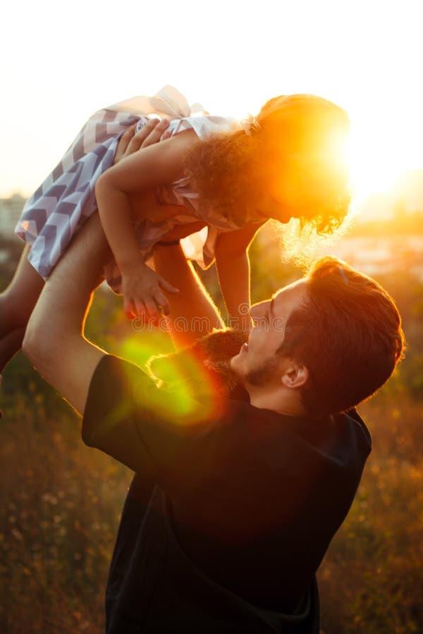 家庭画象四在与小女孩的秋天森林公园孪生 愉快的人民,微笑和亲吻 温暖的晚上阳光 图库摄影