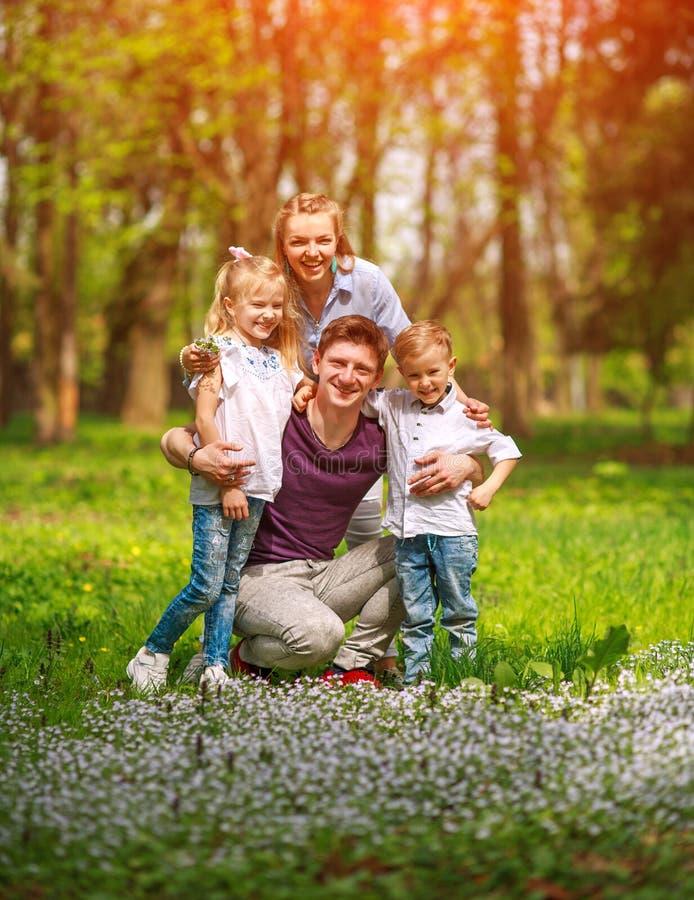家庭画象获得乐趣在开花的城市公园在一起愉快地花费他们的悠闲时间的明亮的好日子户外 免版税库存照片