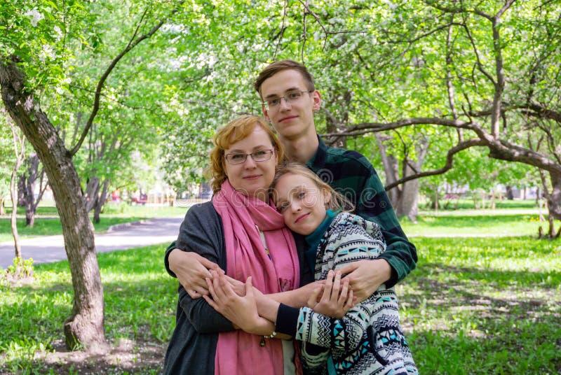 家庭画象-有两面少年儿童的母亲在公园 免版税库存图片