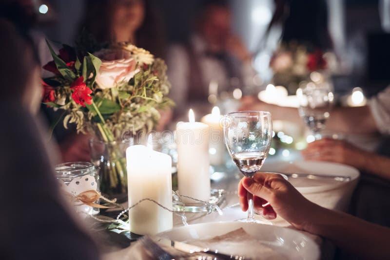 家庭的中央部位在桌上坐一室内生日宴会,拿着玻璃 免版税库存图片