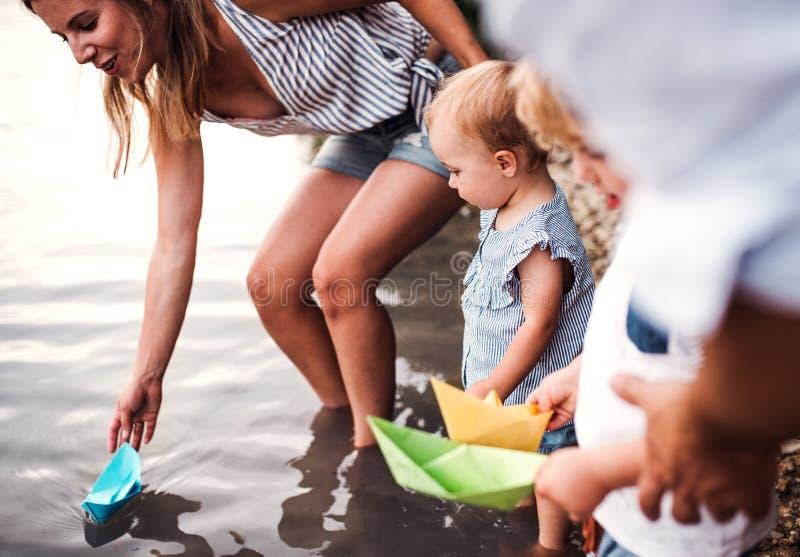 家庭的中央部位有户外两个小孩孩子的由河在夏天 免版税库存图片