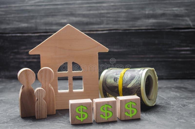 家庭的木图在木房子、价牌和金钱附近站立 买卖房子 好的生活 免版税图库摄影