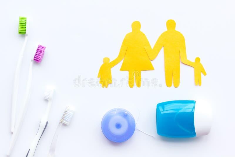 家庭的每日口腔卫生 牙刷、牙线和家庭形象在白色背景顶视图 库存图片